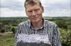 Tom holds homemade briquette made from unwanted junk mail